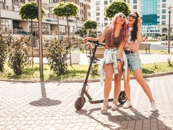 Two young beautiful smiling hipster female in trendy summer clothes.Sexy carefree women posing in the street with pink hair. Positive pure models having fun at sunset. Using electric Kick scooter