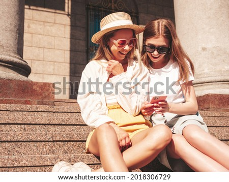 Two young beautiful smiling hipster female in trendy summer clothes.Sexy carefree women posing in the street. Positive models having fun, hugging.They looking at smartphone screen, using apps