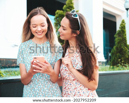 Two young beautiful smiling hipster female in trendy summer clothes.Sexy carefree women posing in the street. Positive models having fun, hugging.They looking at smartphone screen, using phone apps