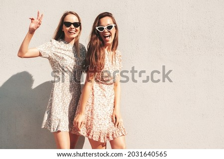 Two young beautiful smiling hipster female in trendy summer clothes.Sexy carefree women posing in the street. Positive pure models having fun at sunset, hugging and going crazy. Happy and cheerful