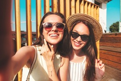 Two young beautiful smiling hipster female in trendy summer clothes.Sexy carefree women posing on the street background in hat. Positive pure models having fun at sunset, taking Pov selfie