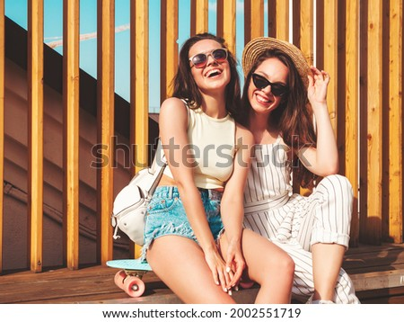Two young beautiful smiling hipster female in trendy summer clothes.Sexy carefree women posing on the street background in hat. Positive pure models having fun at sunset, hugging and going crazy