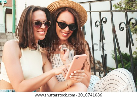 Two young beautiful smiling hipster female in trendy summer clothes.Sexy carefree women posing on the street background.Positive models using smartphone apps, looking at screen