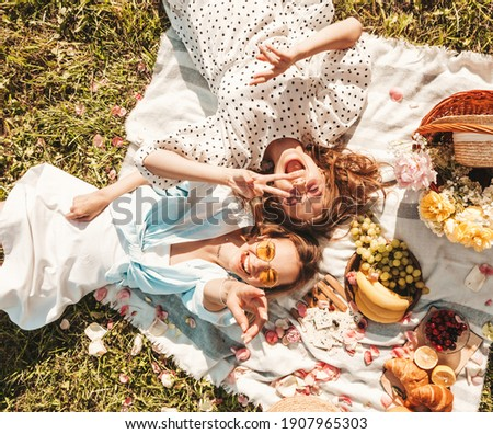 Two young beautiful smiling hipster female in trendy summer sundress and hats.Carefree women making picnic outside.Positive models sitting on plaid on grass, hugging, eating fruits and cheese