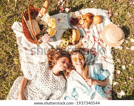 Two young beautiful smiling hipster female in trendy summer sundress and hats.Carefree women making picnic outside.Positive models sitting on plaid on grass, hugging, eating fruits and cheese.Top view