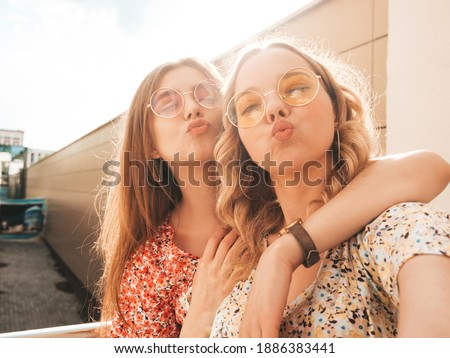 Two young beautiful smiling hipster female in trendy summer sundress.Sexy carefree women posing on the street background. Positive models taking selfie photos, and make duck face