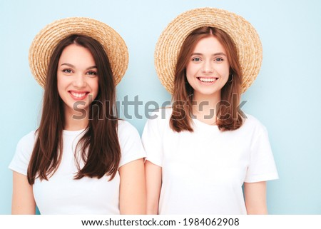 Two young beautiful smiling hipster female in trendy summer white t-shirt and jeans clothes.Sexy carefree women posing near light blue wall in studio.Positive models in hats. Happy and cheerful