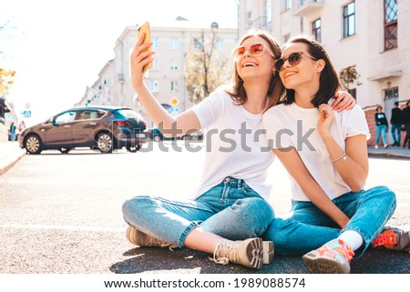 Two young beautiful smiling hipster female in trendy summer white t-shirt clothes and jeans.Sexy carefree women posing on the street background.Positive models going crazy,hugging.Taking photo selfie