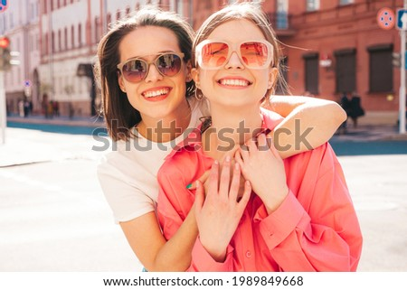 Two young beautiful smiling hipster female in trendy summer white t-shirt clothes and jeans.Sexy carefree women posing on the street background. Positive models having fun, hugging and going crazy