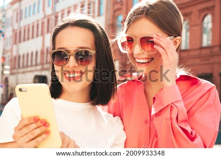 Two young beautiful smiling hipster female in trendy summer white t-shirt clothes and jeans.Sexy carefree women posing on the street background.Positive models using smartphone apps, looking at screen