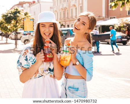 Two young beautiful smiling hipster girls in trendy summer clothes and panama hat.Sexy carefree women posing in the street.Positive models having fun.Drinking fresh cocktail smoozy drink
