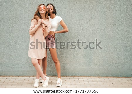 Two young beautiful smiling hipster girls in trendy summer clothes.Sexy carefree women posing on street background in sunglasses. Positive models having fun and hugging