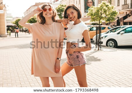 Two young beautiful smiling hipster girls in trendy summer clothes.Sexy carefree women posing on the street background in sunglasses. Positive models having fun and going crazy