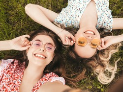 Two young beautiful smiling hipster girls in trendy summer sundress.Sexy carefree women lying on the green grass in sunglasses.Positive models having fun.Top view.Taking selfie photos on smartphone