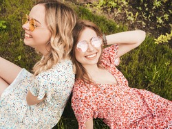 Two young beautiful smiling hipster girls in trendy summer sundress.Sexy carefree women lying on the green grass in sunglasses.Positive models having fun.Top view