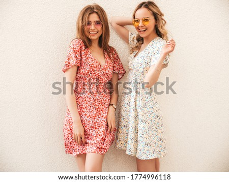Two young beautiful smiling hipster girls in trendy summer sundress.Sexy carefree women posing in the street near wall in sunglasses. Positive models having fun and going crazy