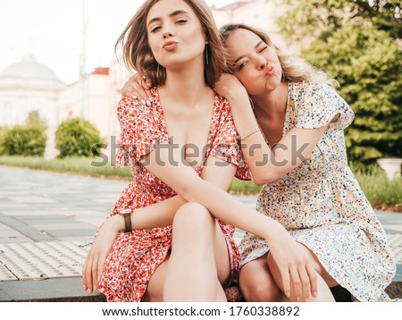Two young beautiful smiling hipster girls in trendy summer sundress.Sexy carefree women sitting on the street background. Positive models having fun and hugging.They make duck face