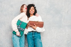 Two young beautiful smiling international hipster female in trendy clothes.Sexy carefree women posing near gray wall.Positive models hugging and giving each other gift boxes.Christmas, x-mas, concept