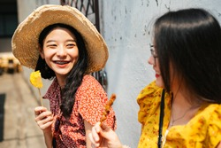 Two young beautiful Thai asian traveler women bestfriend enjoy eating street food in Thailand together.