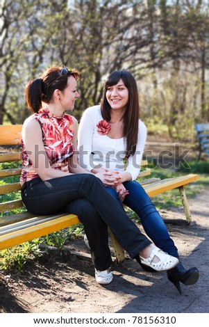 Two young beautiful women chatting on a park bench