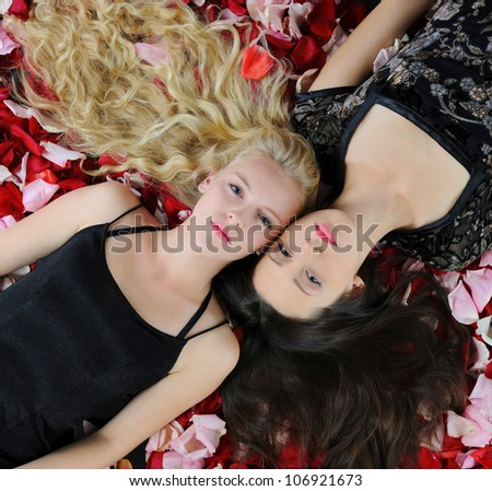 Two young beautiful women in rose petals