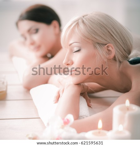 Two young beautiful women relaxing and enjoying at the spa cent #621595631