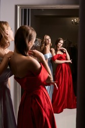 Two young beautiful women wearing off-the-shoulder full-length sky blue and crimson red satin slit prom ball gowns. Models looking in mirror.