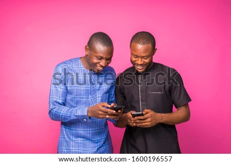 Two young black business men wearing native wears and working on some business proposals on their phones