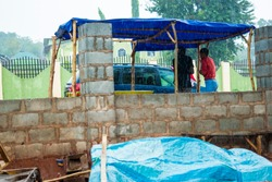 two young black people taking shelter under a roadside vendor stand waiting for rain to stop falling