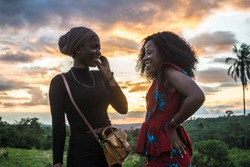two young black women having a conversation outdoors during sunset