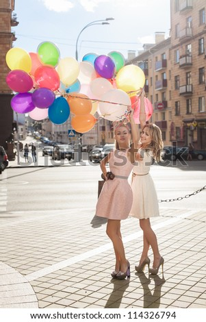 Two young blond women with colorful balloons, urban scene, outdoors