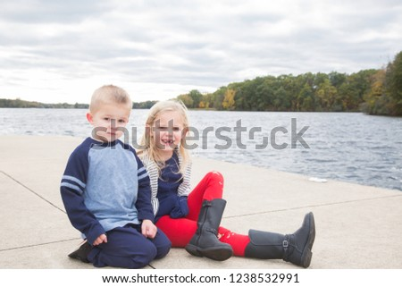 Two young blonde haired, brown-eyed siblings, a boy and girl, sit together on a cement pier. Rippling lake water, a winding tree line and gray cloudy sky fill the background.