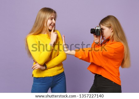 Two young blonde twins sisters girls in vivid colorful clothes taking pictures on retro vintage photo camera isolated on violet blue background. People family lifestyle concept. Mock up copy space