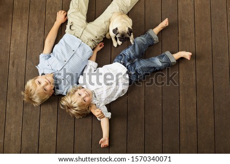 Two young boys and their dog laying on wooden decking