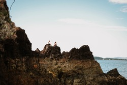 Two young boys climbing rocks by the beach at Coral Beach near Shute Harbour in the Whitsundays, Queensland Australia