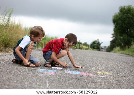 two young boys drawing with sidewalk chalk - family and kids