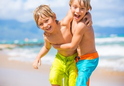 Two young boys having fun on tropical beach, happy best friends playing