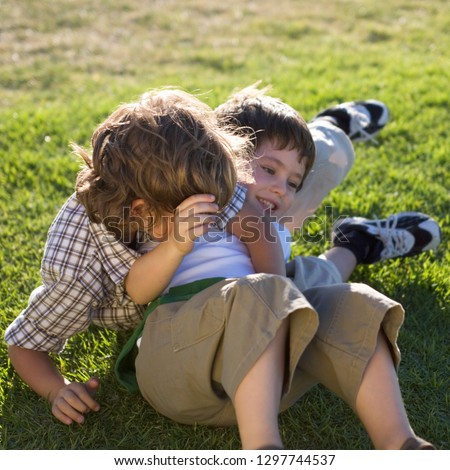 Two young boys having fun playing on grass together