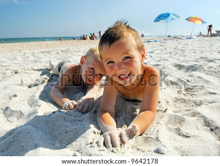 Two young boys lying on the beach