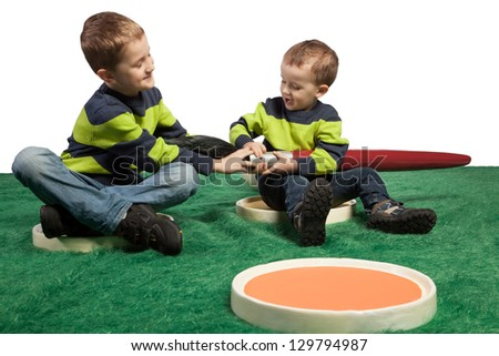 Two young boys pulling at a big brush while both sitting in two big palettes.