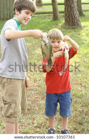 two young boys showing off their catch