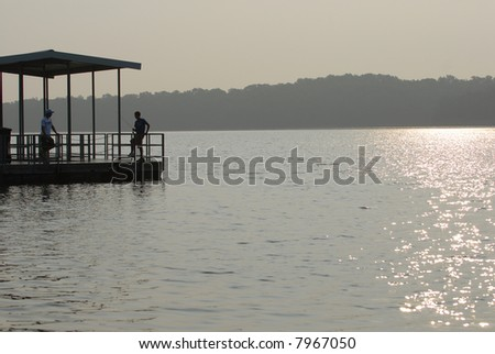 Two young boys talk on a fishing dock on a hazy late afternoon day.