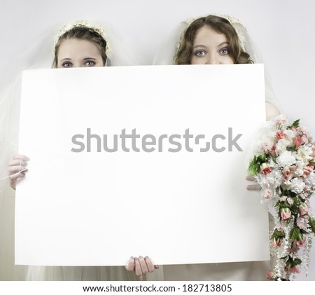 Two young brides holding blank sign up to the their noses