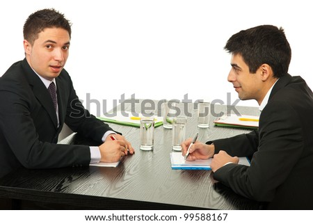 two young business men talking at meeting together and sitting on chairs at table stock photo. Black Bedroom Furniture Sets. Home Design Ideas