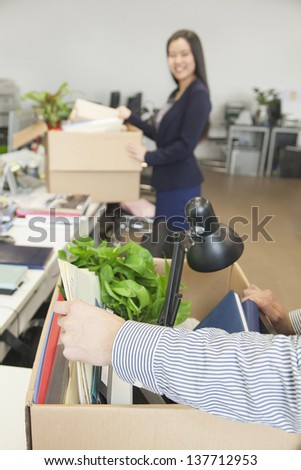 Two young business people carrying boxes with office items