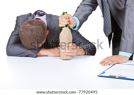 Two young business people in elegant suits sitting at desk drunk with bottle of wine. Isolated over white background. Alcoholism concept.