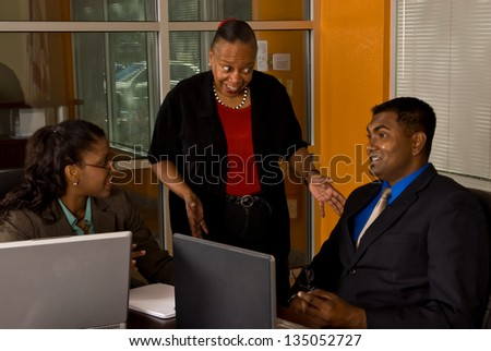 Two young business professionals smile as their more mature, wiser officer manager explains to them how things should be done.