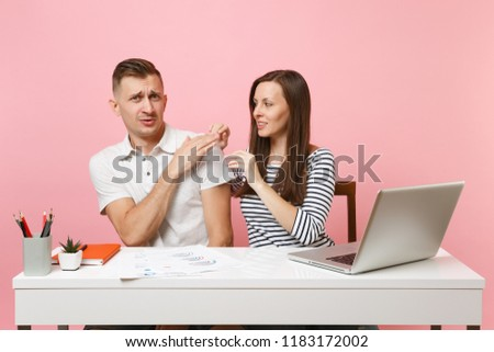 Two young business woman man colleagues sit at white desk isolated on pastel pink background. Sexual harassment, assault lustful boss, intimidation, work ethic, stress, design concept. Co working #1183172002