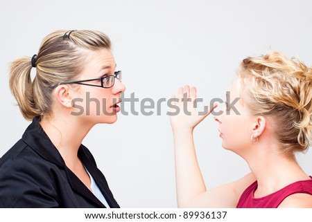 Two young business women conflict.