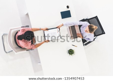 Two young business women in meeting at office table for job application and business agreement. Recruitment and human resources concept. Сток-фото ©